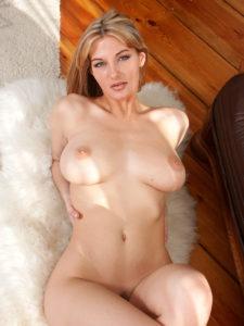 Telephone rose, gros plan sur Nathalie allongée seins nus sur un tapis blanc